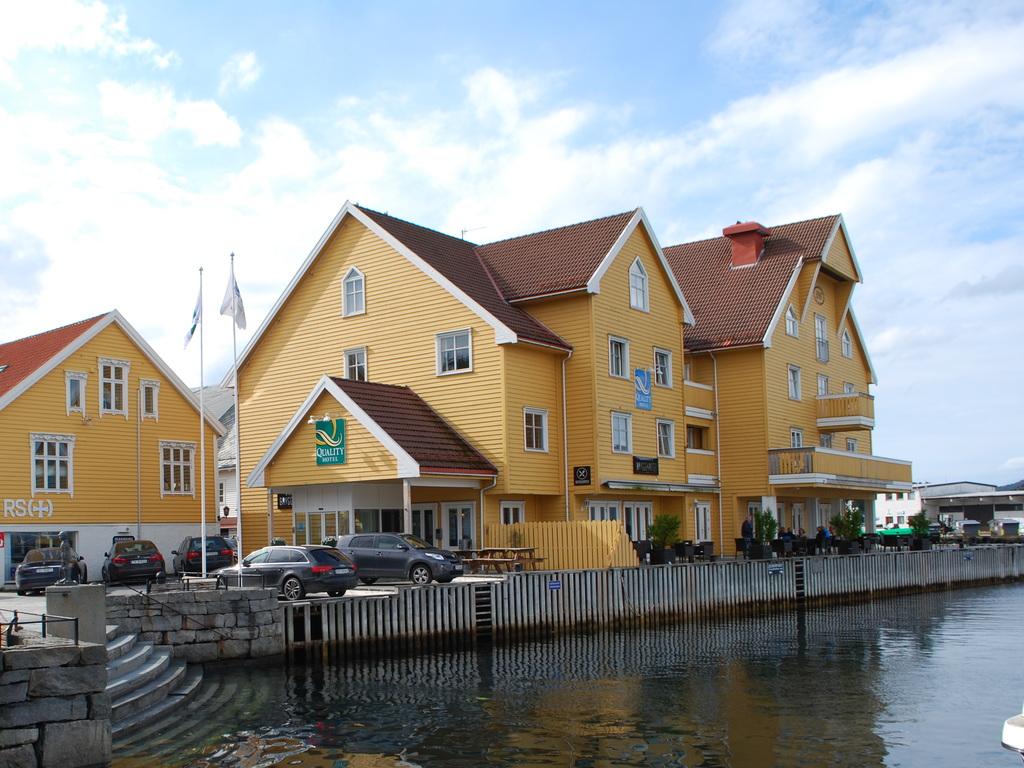 Foto av Quality Hotel Florø ein sommardag. Hotellet er eit gult trebygg og ligg på kaien. Det er blå himmel.