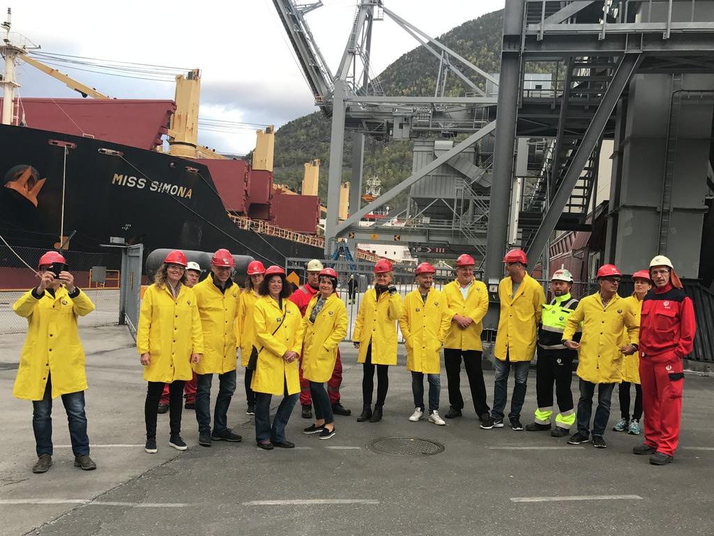 Foto av deltakarane på næringsreisa hausten 2017. Vi ser ein gjeng i gule frakkar og raude hjelmar utanfor Hydro i Årdal. I bakgrunnen ligg det ein stor båt til kai.