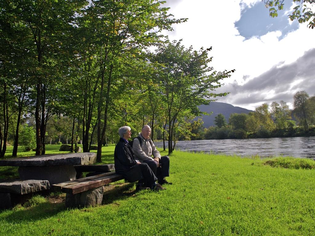 Foto av ein eldre mann og ei eldre kvinne som sit på ein benk ved eit bord i ein veldig grøn park. Det er sol, og vi ser ei elv renne roleg forbi.