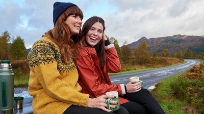 Kaksi naista istuu penkillä tien varrella