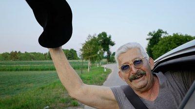 Mies heiluttaa kättä autosta.