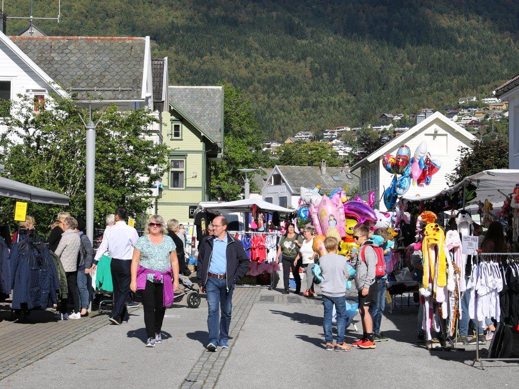 Foto frå Eidsgata på Nordfjordeid ein sommardag med mykje folk og handel.
