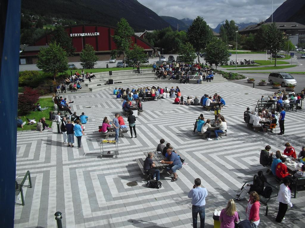 Foto frå den store plassen framfor Stryn vidaregåande skule. Det sit elevar ved borda på plassen, og biletet er teke frå lufta