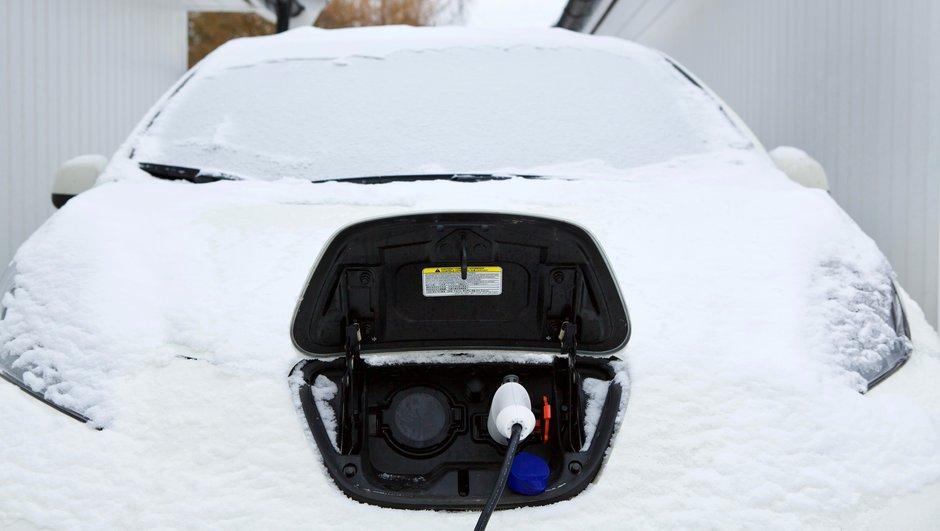 Lumeen peittynyttä sähköautoa ladataan.
