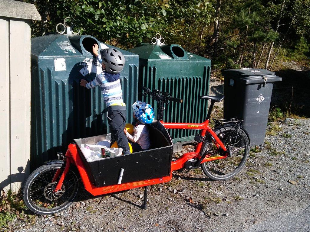 Sommar, to born sit i ei sykkelvogn som er parkert attmed to attvinningsstasjonar for attvinning av glas. Den eine reiser seg og puttar glasflaske opp i den store beholdaren.