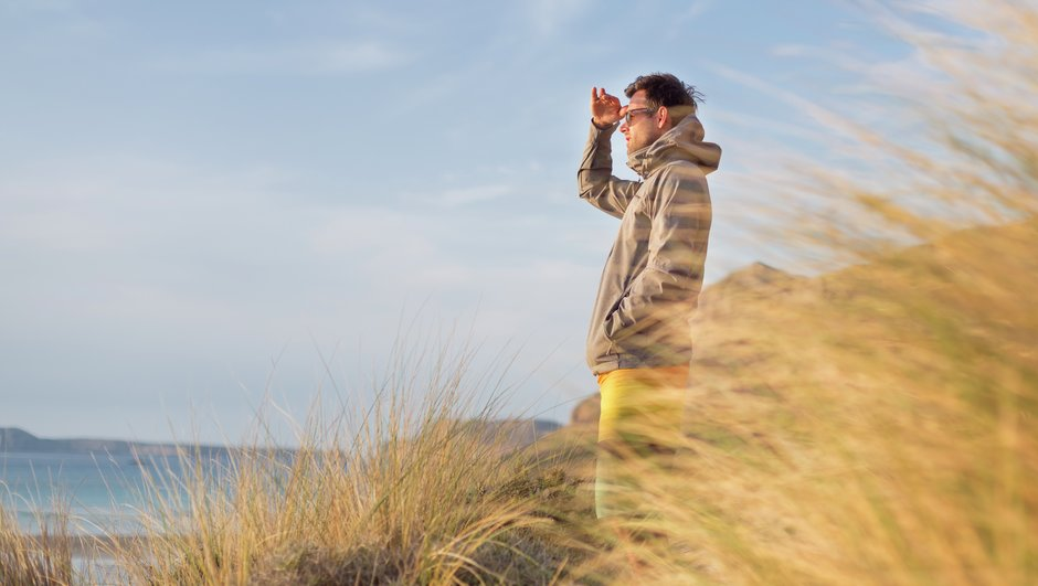 man on the beach watching to horizon