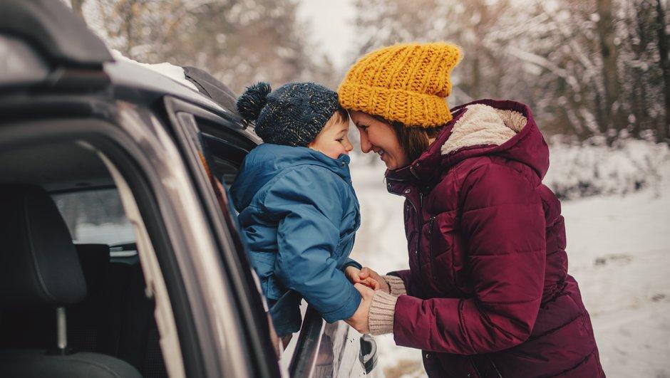 mamma och son vid bil