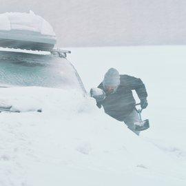 Mies lapioi autoa lumen peitosta