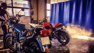 Nainen pesee moottoripyöriä tallissa