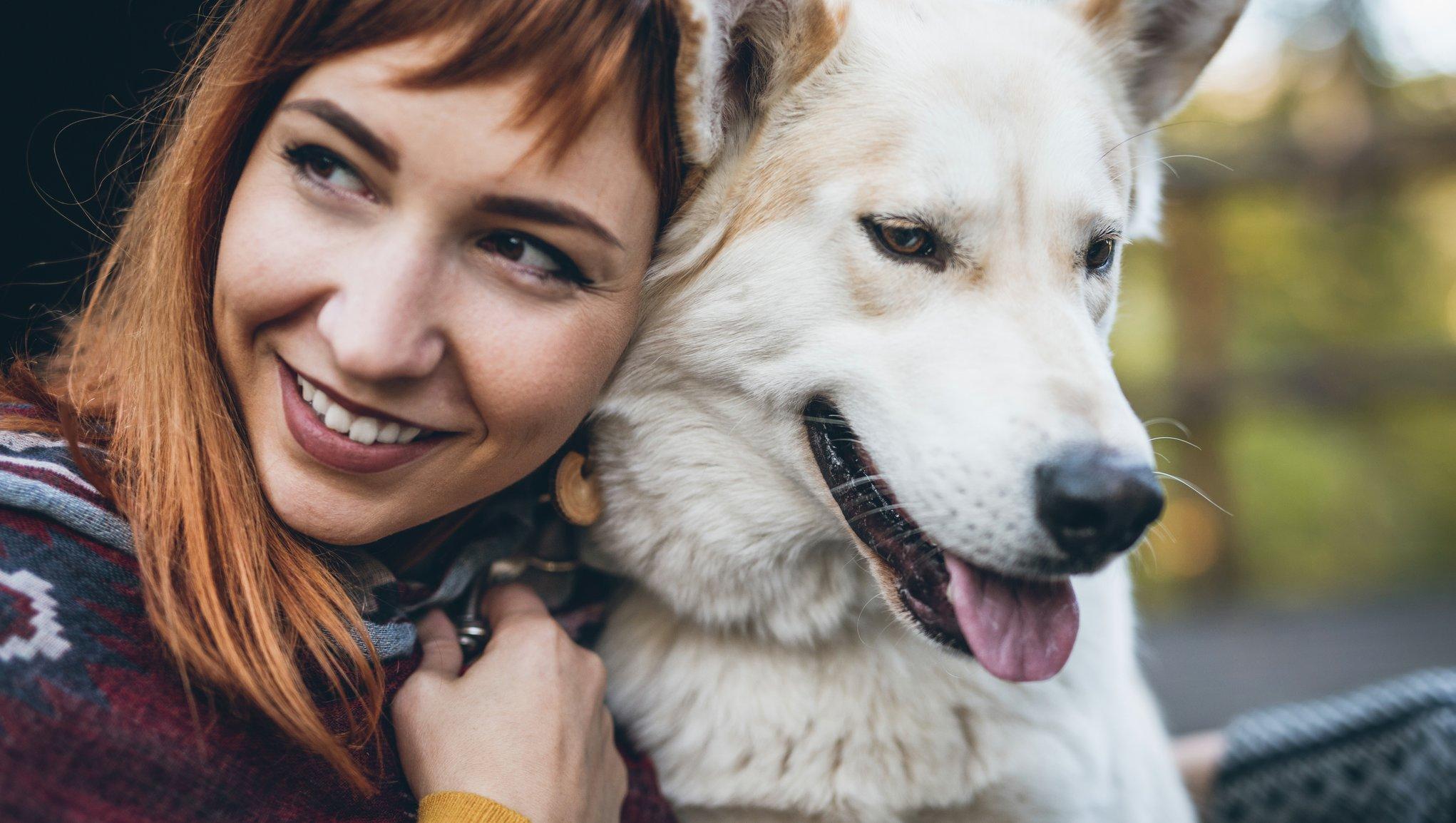 Nainen halaa valkoista koiraa