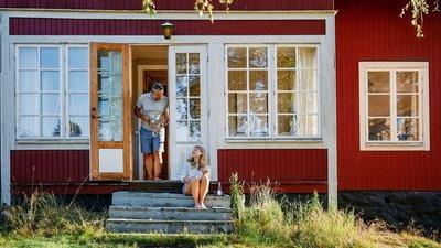 Par som sitter utenfor et rødt hus
