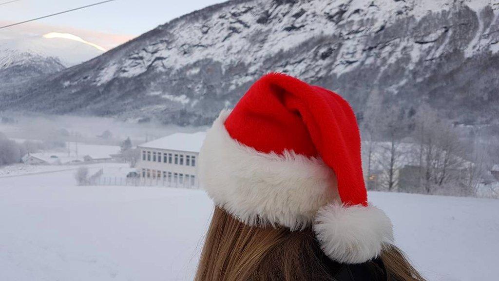 Bilete av jente med nisselue med vinterlandskap og skulehus i bakgrunnen.