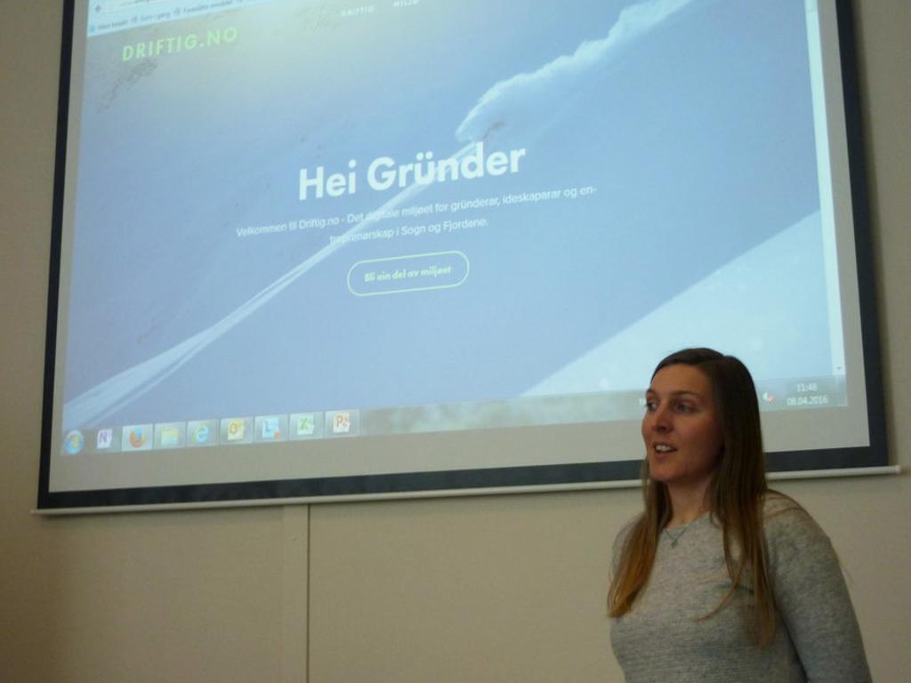 Foto av rådgjevar i fylkeskommunen Ingvild Andersen, som står og snakkar framfor ein stor skjerm på veggen. På skjermen visest nettsida til driftig.no med teksten Hei Gründer.