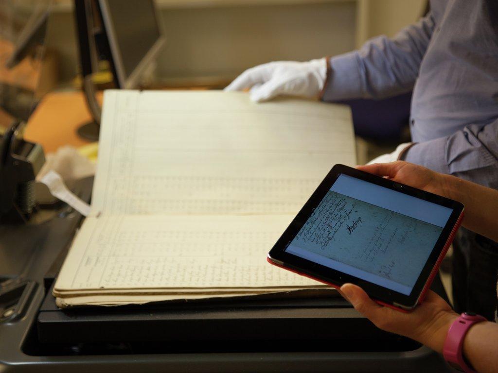 To personar scannar gamal protokoll i bokscannar, og brukar ein ipad til å sjekke resultatet.