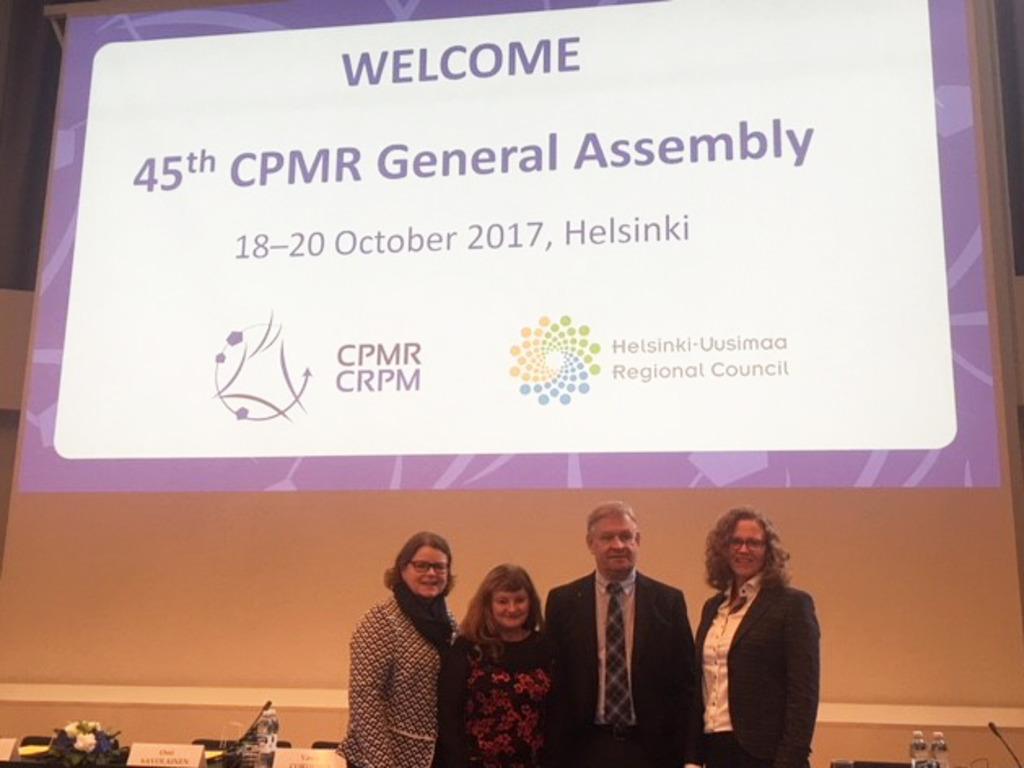 Foto av tre kvinner, ei av dei Åshild Kjelsnes, og ein mann framfor eit lysbilete på veggen der det står Welcome 45th CPMR General Assembly 18-20 October 2017, Helsinki