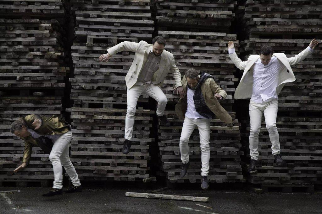 Bandet Good Time Charlie. Fire menn i lyse dressar hoppar ned frå stablar med pallar i bakgrunnen.