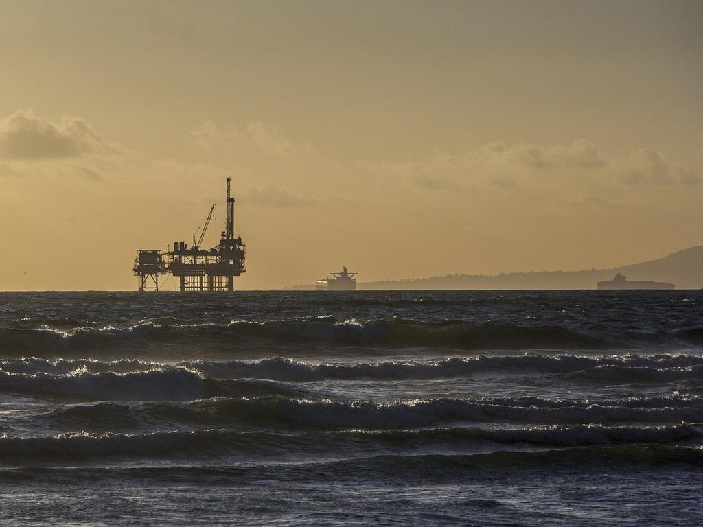 Foto av ei oljeplattform litt på avstand. Vi ser også eit par skip i horisonten.