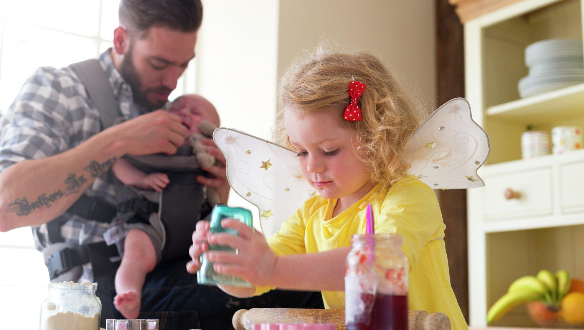 barn leker och pappa matar bebis