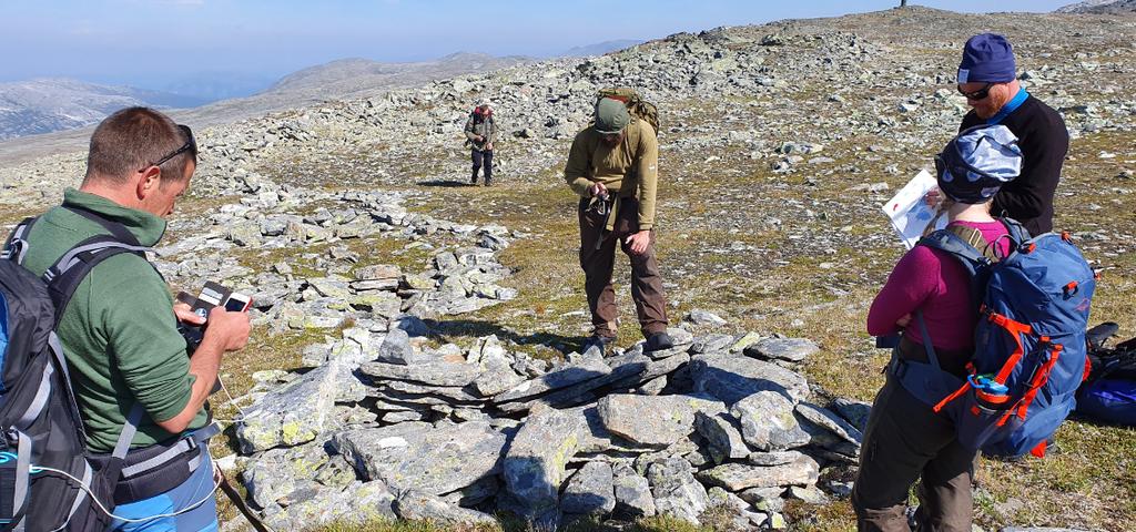 Foto av personar som dokumenterer fangstanlegg på Aurlandsfjellet.