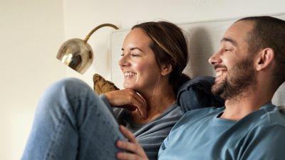 Par tittar på tv i sängen