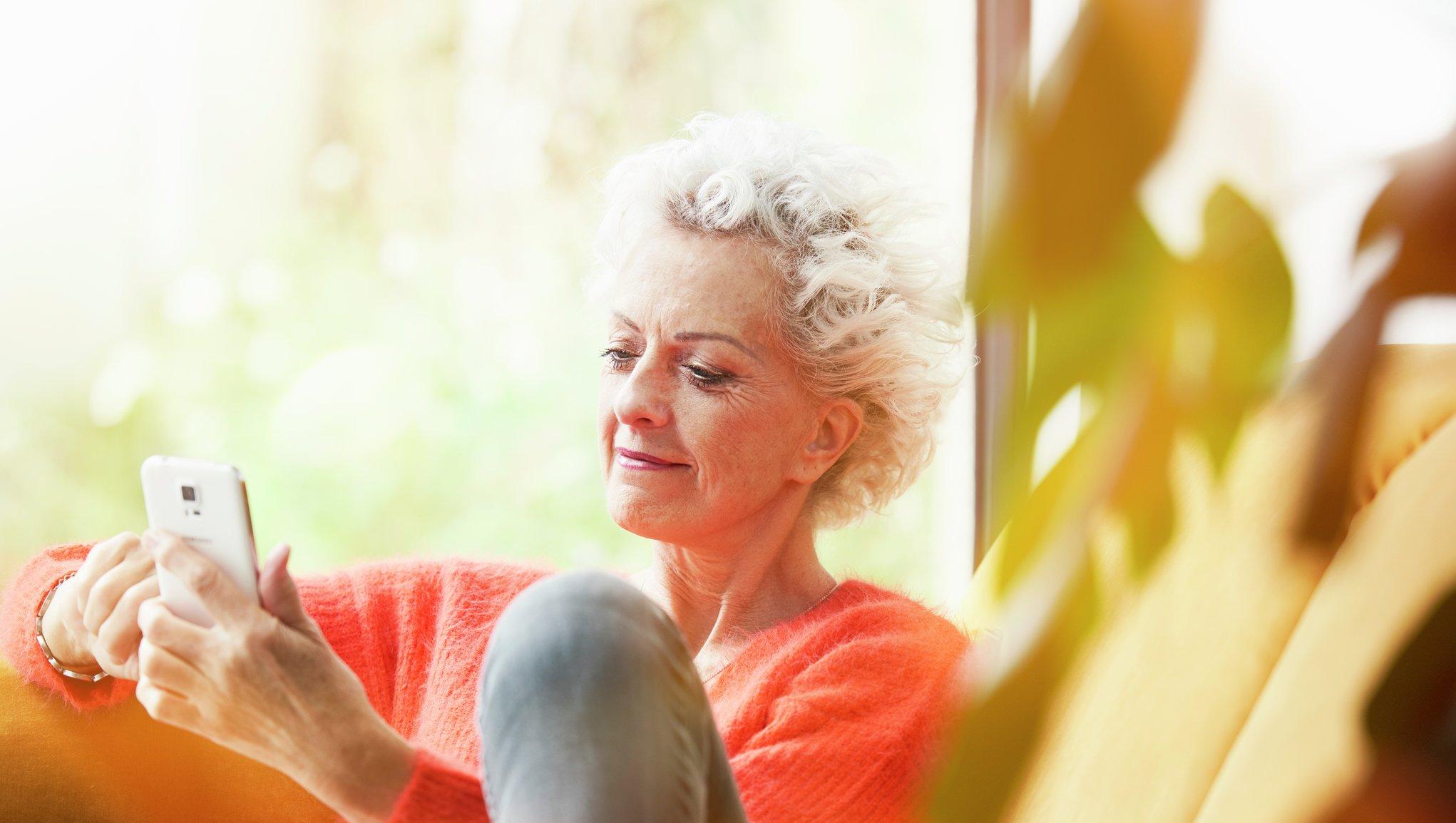 Pensjonsforsikring Kvinne som sitter i sofaen og ser på mobiltelefonen