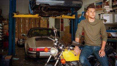 Mies autotallissa moottoripyörän kanssa