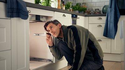 Mies katsoo keittiön kaapin sisään