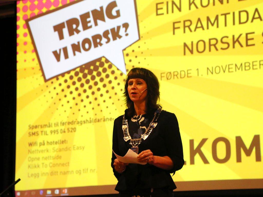 Fylkesordførar Jenny Følling opnar språkkonferansen i Førde 2018. Det står Treng vi norsk? på lerretet bak henne.