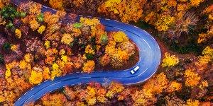 Auto ylhäältä kuvattuna mutkaisella tiellä
