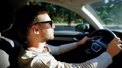Mies ajaa autolla aurinkolasit päässään
