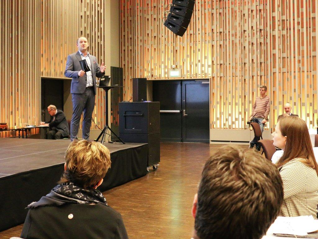 Foto av samferdsleminister Jon Georg Dale på scena under Nasjonal rassikringskonferanse i 2019. I framkant ser vi bakhovudet til enkelte i publikum.