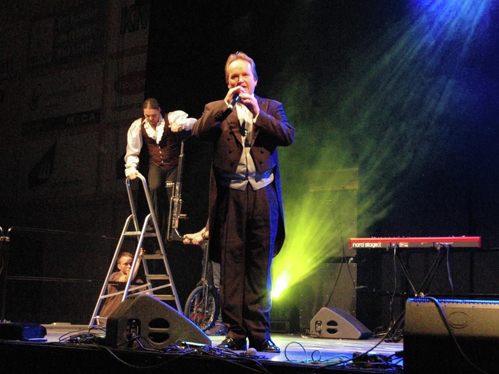Foto av ein festkledd sirkusdirektør, Jan-Ketil Smørdal, som snakkar i ein mikrofon. Bak han ser vi den svenske sykkelartisten Malte Knapp, som står på ei gardintrapp for å kome seg opp på den høge sykkelen sin.