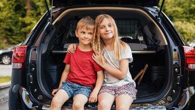 Nuori poika ja tyttö istuvat pysäköidyn auton tavaratilan reunalla.
