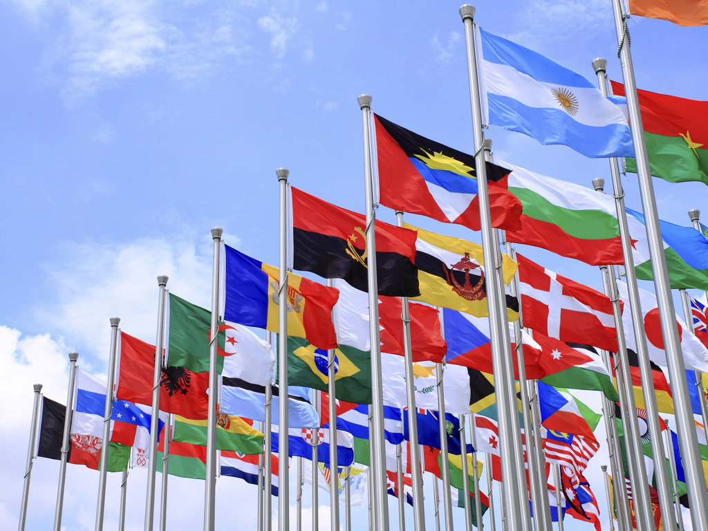 Foto av mange lands flagg som heng i flaggstenger. Biletet er teke nedanfrå, og bak flagga ser vi blå himmel