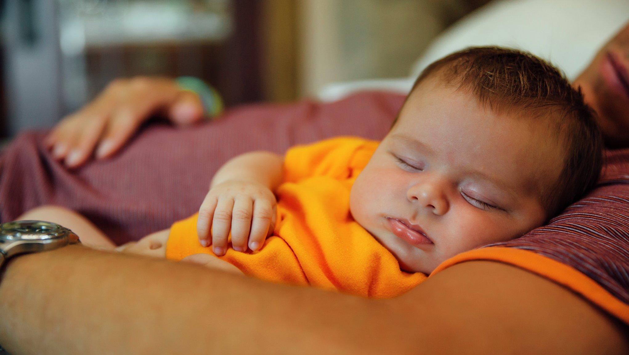 mies nukkuu vauva sylissään