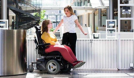 Kvinne i rullestol i atrium har bok på fanget og snakker med assistent