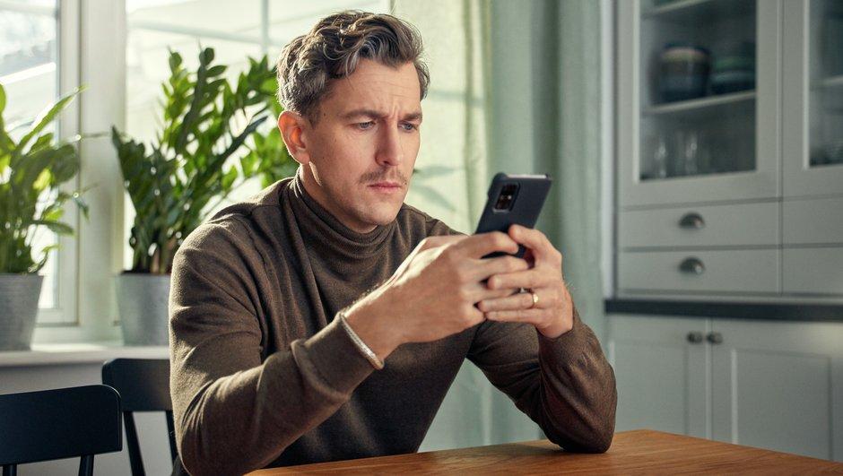 mies katsoo puhelintaan