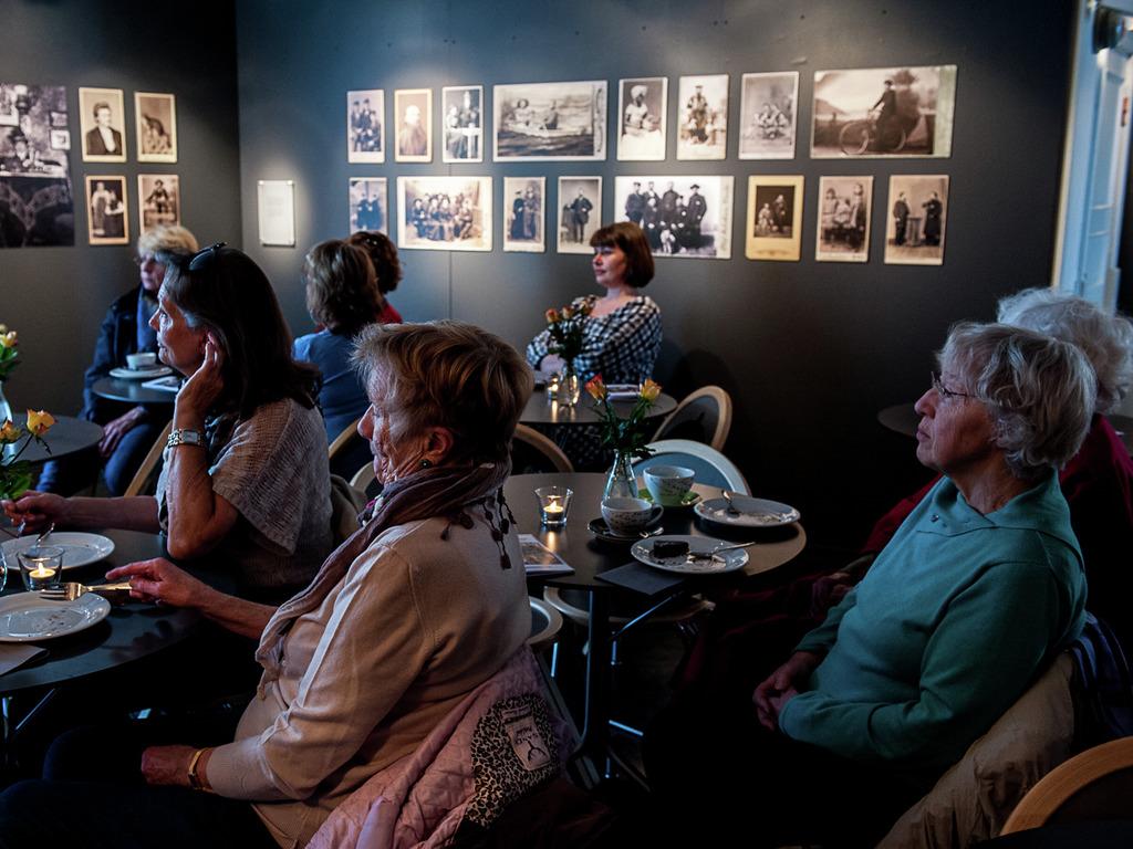 Foto som syner ei forsamling stort sett eldre damer. Dei sit vende mot venstre, der det føregår noko utanfor biletet. Dei sit ved små bord, med tallerknar og kaffikoppar framfor seg.