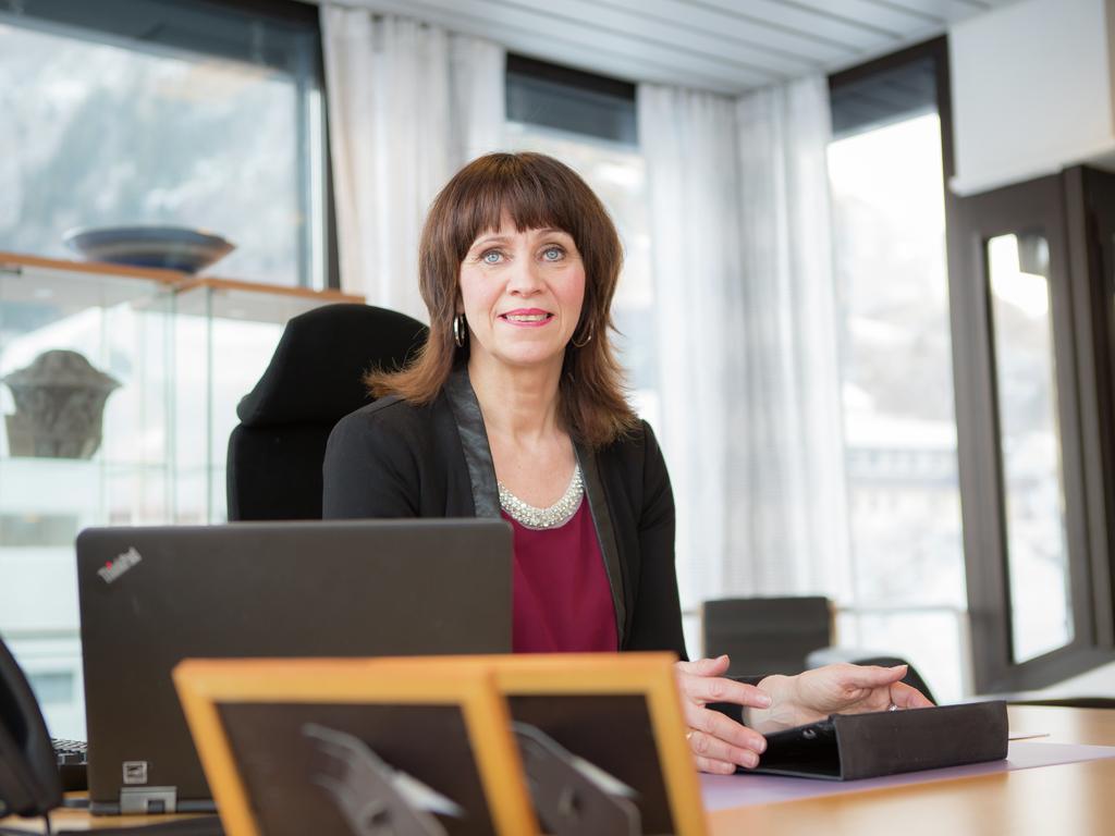 Foto av fylkesordførar Jenny Følling, som sit ved kontorpultet sin. Ho har pc, diverse papir og biletråmer framfor seg og er kledd i ein svart blazer med burgunder topp under. title=