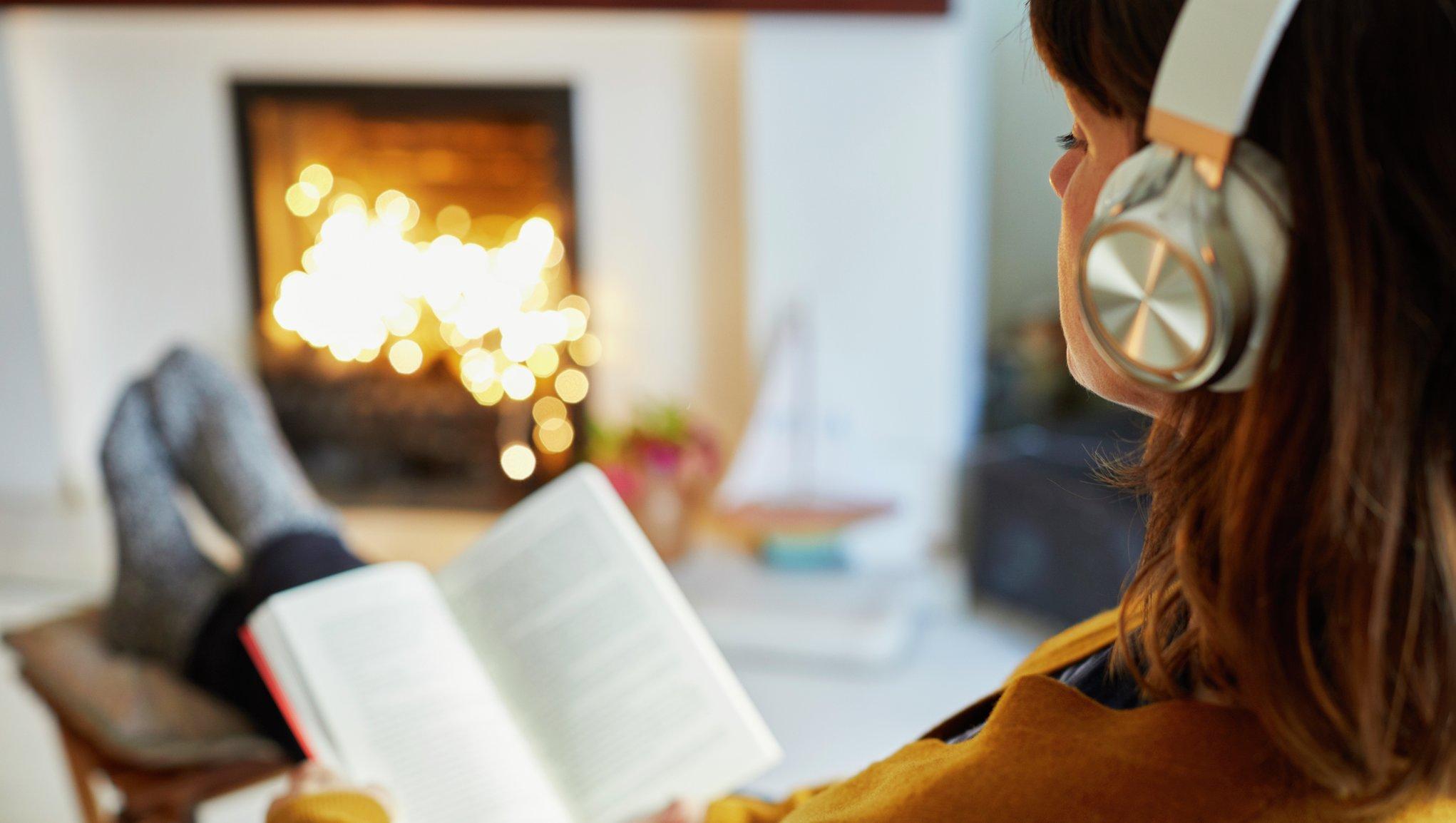Nainen lukee kirjaa takkatulen ääressä
