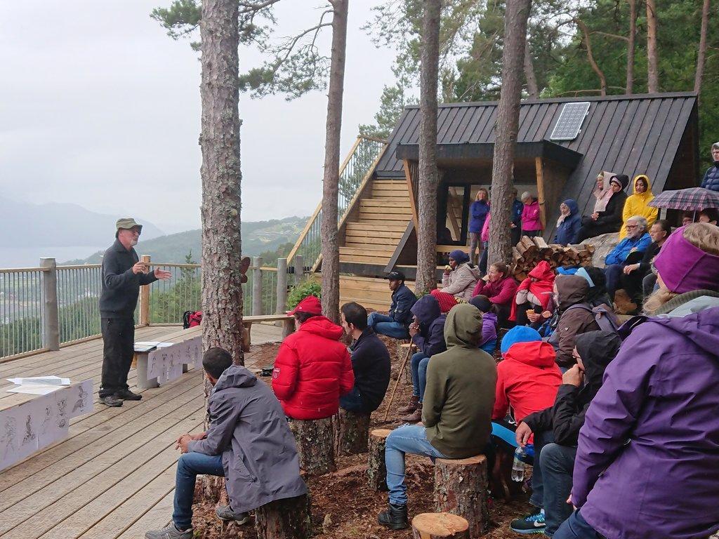 Rolf Losnegård held framsyning framføre dagsturhytta på Sandane. Mange sit i regntøy og høyrer på.