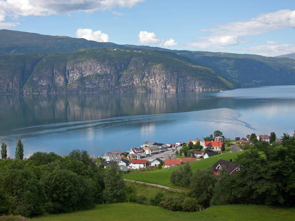 Foto med utsyn over Utvik i Stryn ein sommardag med blå himmel og berre litt skyer. Vi ser ned mot sentrum og fjorden.