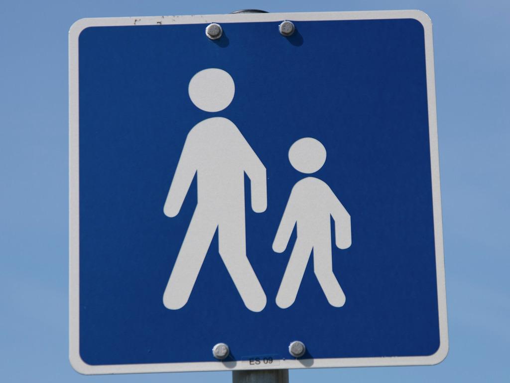 Foto som syner eit trafikkskilt som symboliserer skuleveg. Det er eit blått skilt med kvit ramme og ein stor og ein liten person også i kvitt.