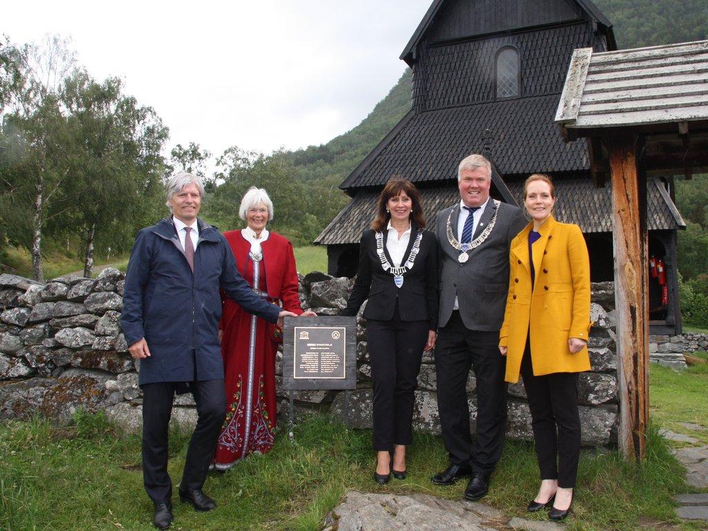Fem finkledde personar står ved ein plakett utanfor Urnes stavkyrkje.