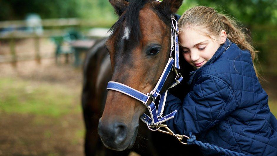 tyttö halaa hevosta