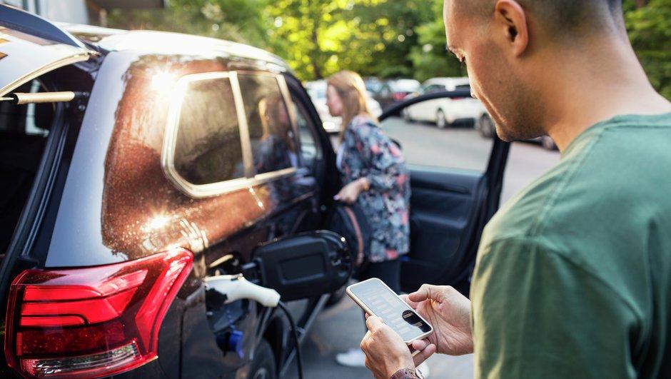 Mies katsoo kännykkää sähköauton latauksen aikana.