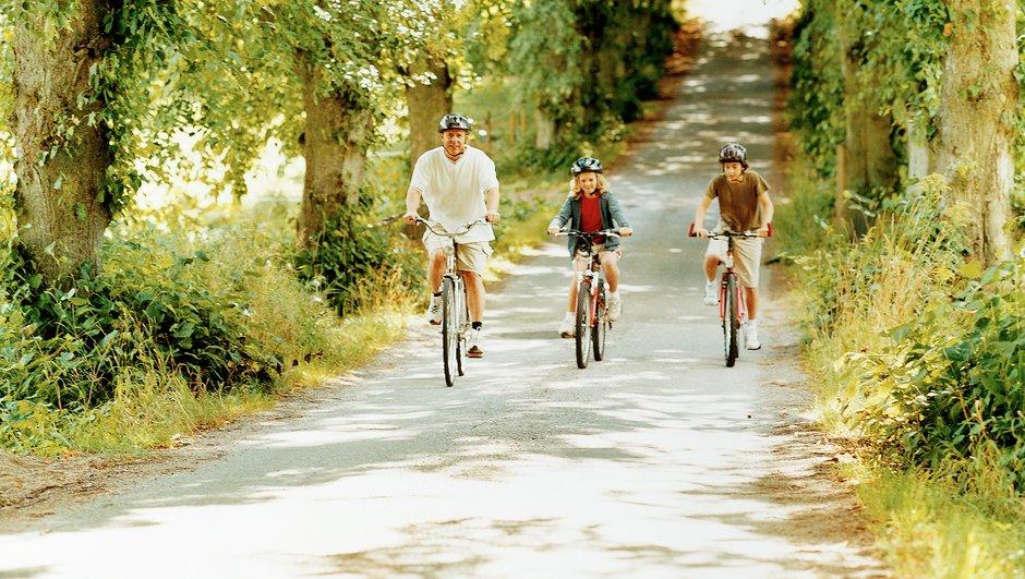 Far og børn cykler på en landevej.