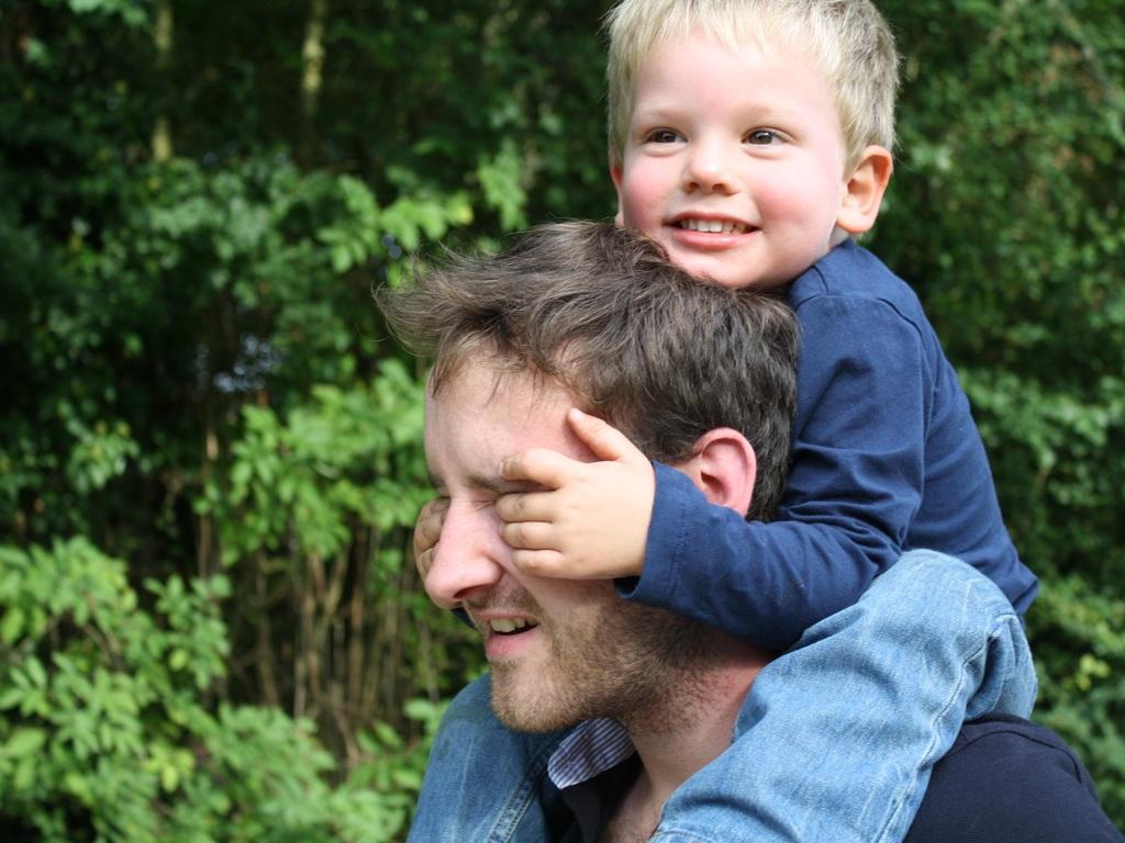Foto av ein liten, lyshåra gut, ca. 2-3 år, som sit på skuldrene til ein vaksen mann og held for augene hans.