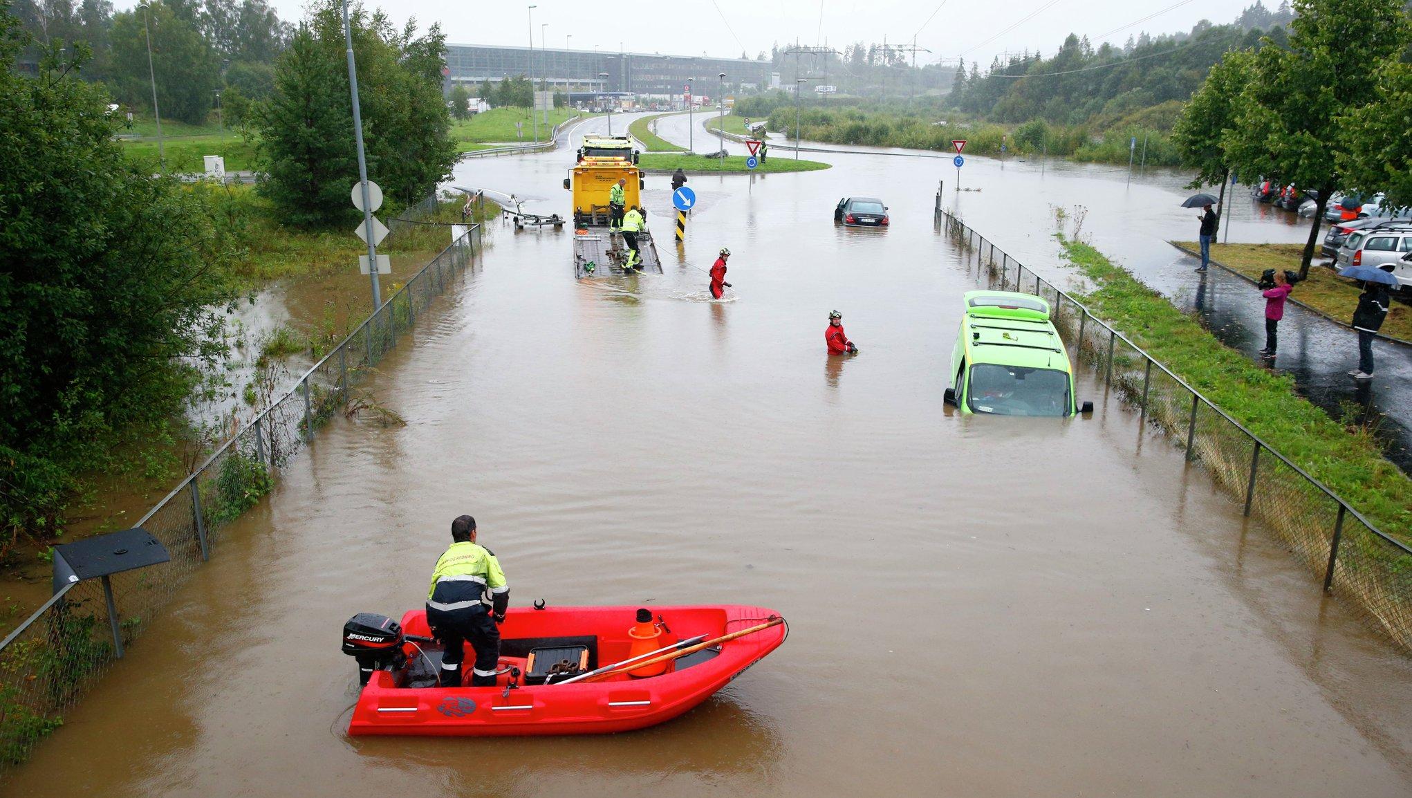 Pelastustyöntekijät auttavat tulvivalla kadulla
