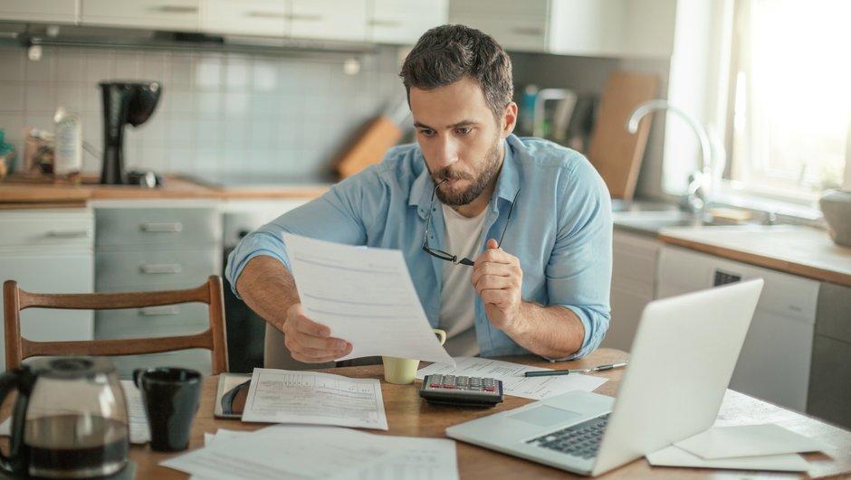 Mann som sitter ved kjøkkenbordet og studerer et dokument